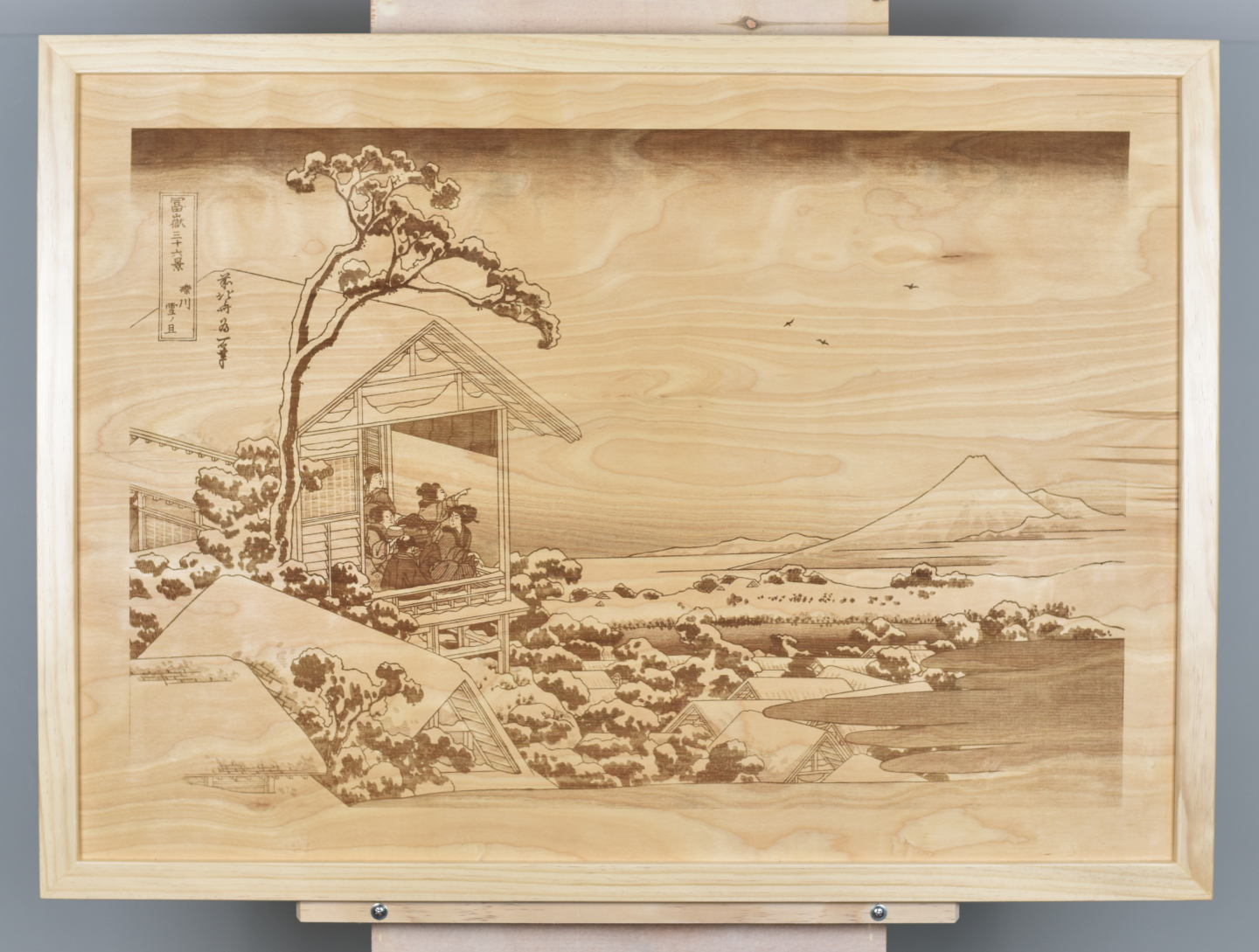 A wood burning (digital pyrograph) of men and women in a teahouse looking at Mount Fuji in the morning after a snowfall. One of the famous Thirty-six Views of Mount Fuji by Katsushika Hokusai.
